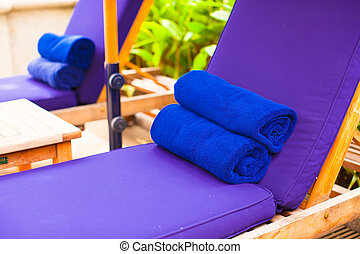 Close-up of towels on the poolside loungers