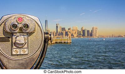 Close up of tower viewer binoculars with blurred New York City skyline
