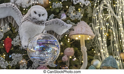 Close-up of toy in the form of flying owl on spruce branch. In the foreground is a large Christmas ball. Decorated christmas tree background. Happy new year concept. Blurred background with lights.