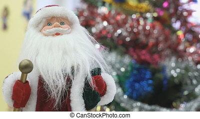 Close up of toy Santa near christmas tree