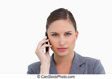 Close up of tradeswoman listening to caller against a white ...