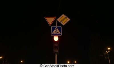 Close-up of traffic lights at night. Traffic signal light changes from red to green at night.