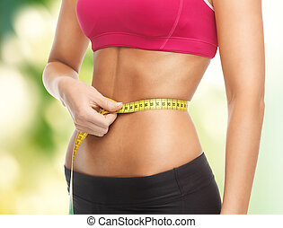 trained belly with measuring tape - close up of trained...