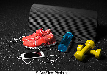Close-up of training shoes, rubber mat, dumbbells, blue bottle and telephone on a black spotted background. Copy space.