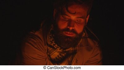 Close-up of traveler's face with a beard resting by the fire at night