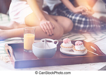 Close up of tray with cake and drink lying on the bed