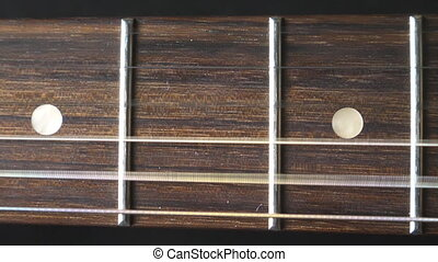 Close up of trembling guitar strings against fret. Chords...