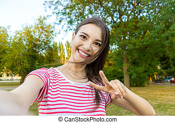 Close-up of trendy girl face is making selfie photo.