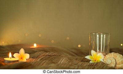 Close up of tropical flowers for home decor. Slill life, candle lights and plumeria frangipani flowers on a soft textile