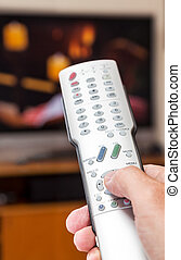 Close up of TV remote control with television