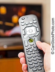 Black modern TV remote control being pressed by thumb with out of focus screen background
