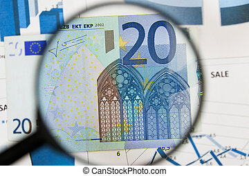 Close-up of twenty euros through a magnifying glass. Business background. Money research concept.