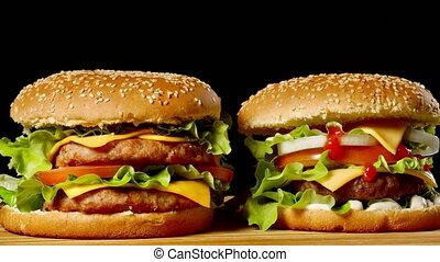 Close-up of two appetizing burgers with sesame buns rotating...