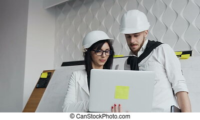 Close up of two architects or engineers discussing a project in a white office. They are wearing white and white hard hats and looking at a laptop screen