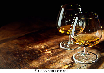 Close up of two bourbon filled glasses on table