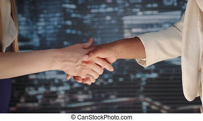 Close up of two business women shaking hands with each other