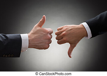 Businesspeople Hands Showing Thumb Up And Thumb Down - Close...