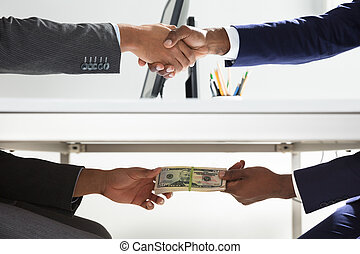 Two Businesspeople Shaking Hand And Taking Bribe