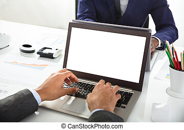 Close-up Of Two Businesspeople Working On Laptop