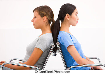 Close-up of two businesswoman sitting in chairs to back