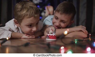 Close-up of two children lying on the floor near the Christmas tree and shaking a snow globe in the middle of which is the Santa Claus. Concept of winter and Christmas gifts