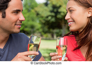 Close-up of two friends happily looking at each other while smiling and holding glasses of champagne in a sunny park
