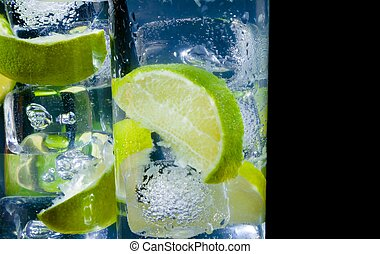 close-up of two glasses with cocktail and ice with lime slice on black background with space for text, disco club atmosphere