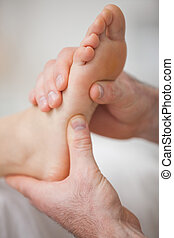 Close-up of two hands massaging a foot in a room