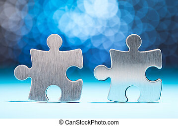 Close-up Of Two Silver Jig Saw Pieces With Bokeh Background