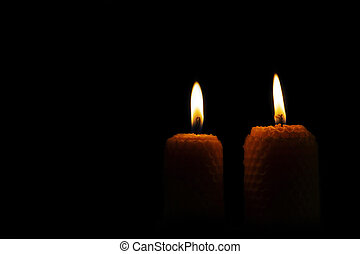 Close-up of two lit yellow candles on a black background.