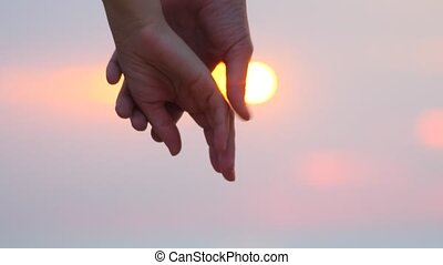 Close-up of hands joining together with sunlight flare in the background. Beautiful romantic moment between two lovers. Feelings, emotional romantic cinematic scene. First love, falling in love
