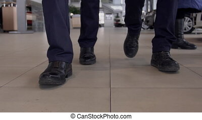 Close up of two male legs walking throught autocenter, slow...