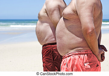 Close up of two obese fat men of the beach