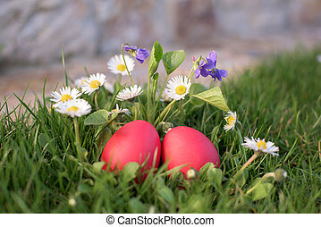 Close up of two red Easter eggs among flowers