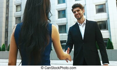 Close up of two satisfied partners shaking hands outdoors near the office.