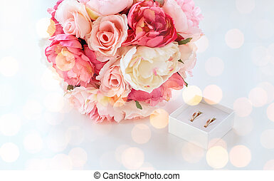 close up of two wedding rings and flower bunch