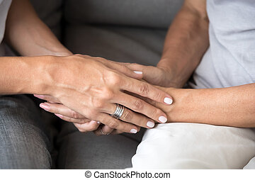 Close up of two women holding hands