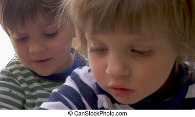 Close up of two young children a boy and girl focused on...