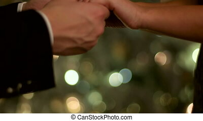 Close up of two young people holding hands on New Year day.