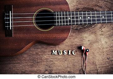 Close up of ukulele and earphone on old wood background