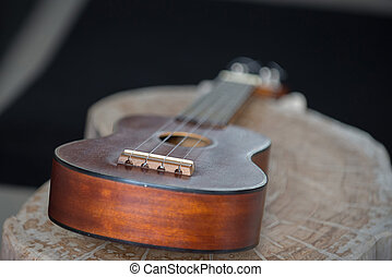 Close up of ukulele on old wood background with soft light, Vintage tone