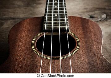 Close up of ukulele on old wood background