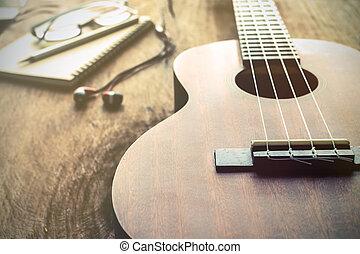 Close up of ukulele on old wood background with soft light