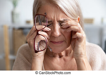 Close up of unhealthy old woman suffer from migraine - Close...