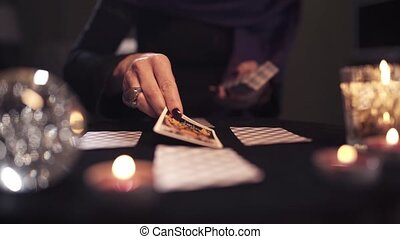Close-up of unidentified middle-aged sorceress woman with dark manicure and ring lays fortune-telling cards on dark table with candles and with glass ball. Concept of mythical predictions for future