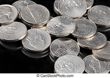 Close up of United States coins, Nickles on black background...