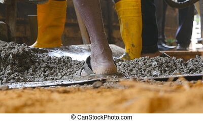 Close up of unrecognizable indian man shoveling manually wet cement in pile at building site. Local builders working on construction area. Concept of future project. Low angle view
