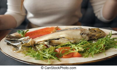 Close up of unrecognizable woman eating fish steak with...