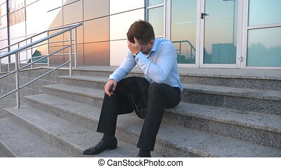 Close up of upset sad manager sitting on stairs near office building and crying. Desperate young businessman got a very bad news on phone and feeling despair outdoor. Concept of financial crisis