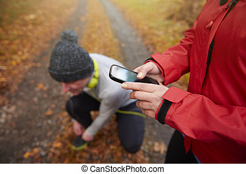 Close up of using phone by one of the runners